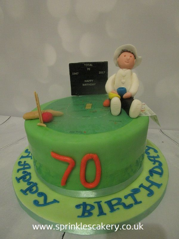 A fondant covered cricket theme cake with edible printing, handmade edible fondant umpire and cocktail sticks for stumps!