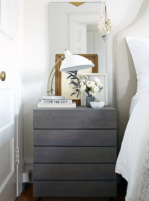A sleek gray-washed nightstand anchors all-white accents of a horizontal book stack, task lamp, frameless mirror and crisp white bedding.