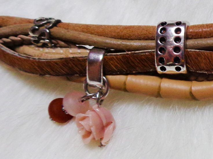 Deze prachtige bruine armband bevat verschillende bandjes die aan elkaar gekoppeld zijn door middel van een sierlijke ring. Aan de armband hangen verschillende bedeltjes waaronder een 'oude' roze roos en kraaltjes. De armband is sierlijk en gemaakt van echt leer.