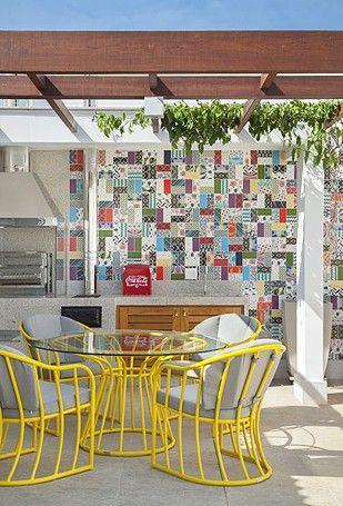 Espaço da churrasqueira, com azulejos bem coloridos e mesa para refeições (Foto: Divulgação)