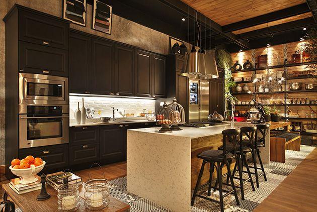 Conjunto dr coisas interessantes numa cozinha: parede de tijolinhos, os ladrilhos ao redor da bancada, com um piso amadeirado, uma mesa de apoio e no fundo uma grande estante.