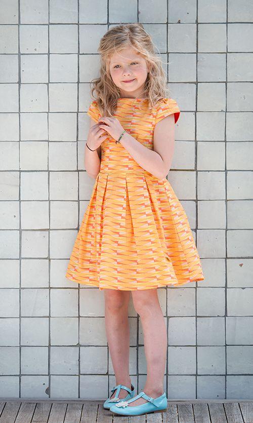 Luchtig zomerjurkje in bijzonder katoenen stofje: Otje Worteltjescake. Zacht okergeel met oranje en mintgroene geometrisch dessin. Voor de bijzondere meid!  #geel #yellow #ocre #oker #mint #oranje #orange #worteltjes #carrots #zomerjurkje #summerdress #kinderkleding #childrensclothing