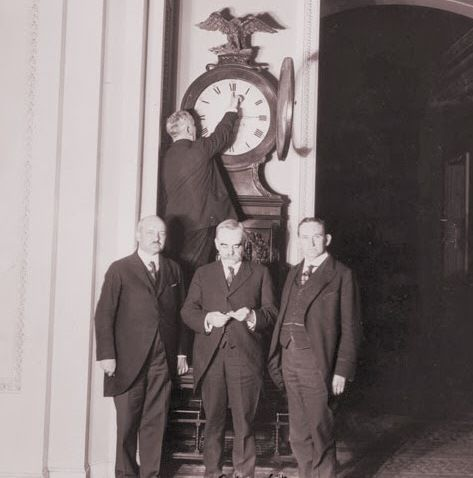 """The Senate Sergeant at Arms turns back the Ohio """"Senate"""" Clock for the first ever daylight savings time back in 1918, while other Senators look on. http://thebigclockstore.com/category/blog/"""