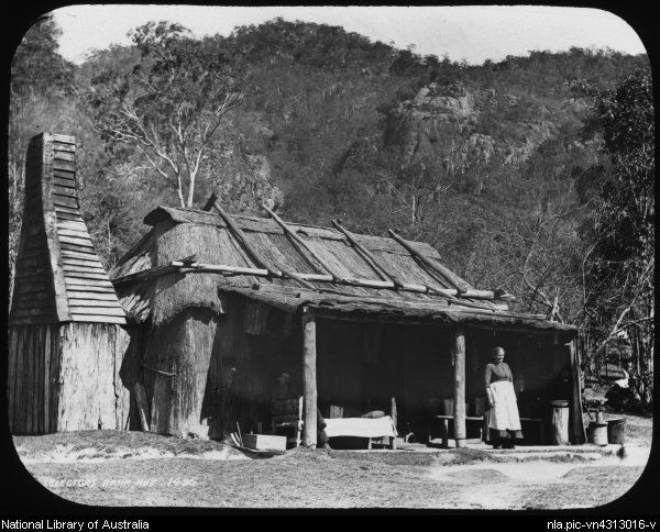 Standing woman and a seated man outside a selector's bark hut, Australia, ca. 1895 [transparency]