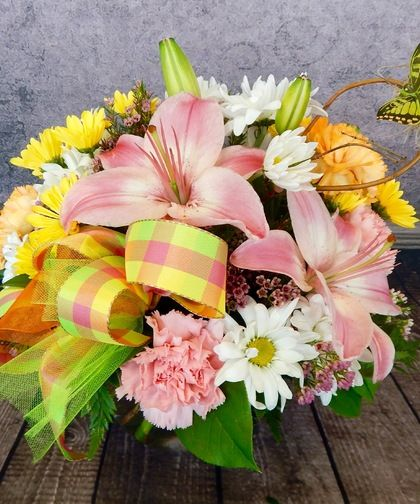 A Child's Wish-Carnations, daisies, lilies and fluffy filler flowers are arranged with ribbon and a fluttery butterfly. #BagoysFlorist #AnchorageFlowers #MothersDay #MothersDayFlowers #MothersDayGifts