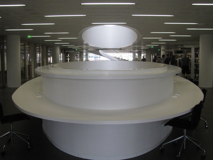 Kaisa Library, Helsinki University. The oval shapes of the central well are used on most floors to provide student desk space, a very efficient and attractive use of space. They appear to be made from a very durable substance like white Corian.