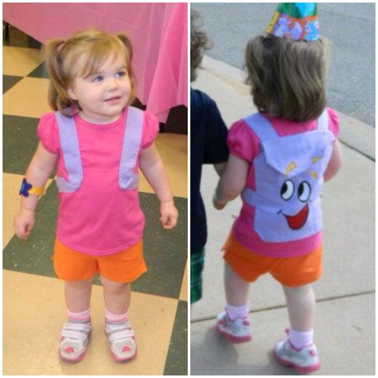 DIY Dora the Explorer Costume. Pink tshirt with purple material sewn on in backpack shape. Painted the face on. Orange shorts and sneakers. Made the bracelet out of felt.