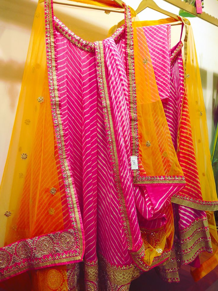 One of my favorites for a mehendi function. This gorgeous mango yellow orange with pink leheriya lehenga is the perfect pick this wedding season. #Frugal2Fab