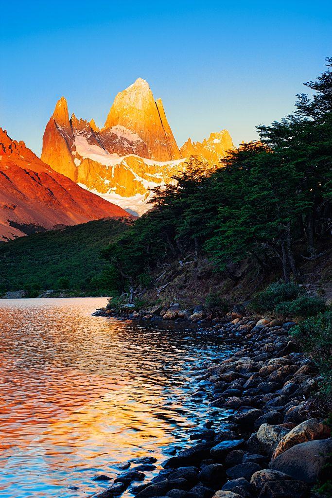 Cerro Fitzroy and Cerro Poincenot illuminated at sunrise, from the shore of Laguna Capri, in Argentina's Los Glaciares national park.