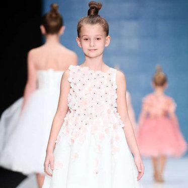Вечернюю моду для самых маленьких предложил на неделе моды в Москве бренд детской одежды Blue Jasmine. Для девочек в коллекции представлены нежно-розовые и голубые платья, напоминающие цветы со множеством лепестков, а для мальчиков - рубашки с бабочками и адаптированные под детскую моду варианты костюмов.