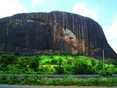 """NIGERIA: Zuma Rock is a large monolith located in Niger State, Nigeria. It is just north of Nigeria's capital Abuja, along the main road from Abuja to Kaduna, and is sometimes referred to as """"Gateway to Abuja."""" Zuma Rock is 725 meters above its surroundings."""