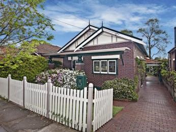 Brick californian bungalow house exterior with picket fence & window awnings - House Facade photo 526881