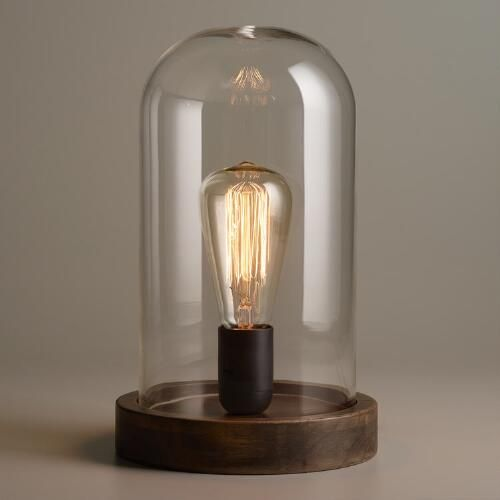 Crafted of glass with a wooden base, our exclusive Edison Glass Cloche Table Lamp is a unique tribute to the classic inventor. Our sculptural Edison filament bulb is encased inside the cloche to complete the industrial look.