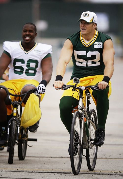Green Bay Packers'Clay Matthews(52) rides a bike with teammateKevin Hughes(68) toNFLfootball training camp Friday, July 26, 2013