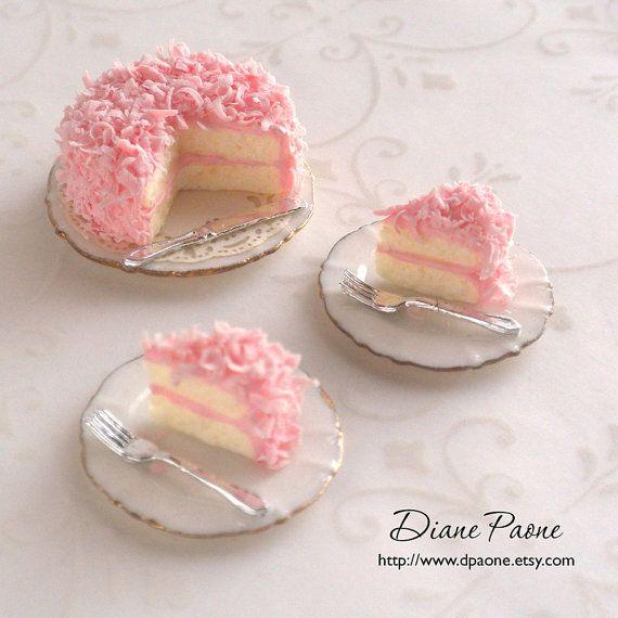 El último pastel coco rosa en un plato de porcelana con un cuchillo y tapetito de papel delicado debajo de él. Dos porciones generosas con horquillas en platos de postre de porcelana. 1:12 escala miniatura casa de muñecas. Usted recibirá el artículo que se muestra exacta. Con amor hechos a mano por mí, Diane Paone, IGMA Artisan.    • Torta de placa mide aproximadamente: 1 x 1/2 pulgadas (25 mm x 12 mm) de altura  • La placa con una sola rodaja medidas aproximadamente: 13/16 x 1/2 de alto (21…