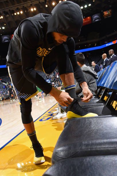 Stephen Curry of the Golden State Warriors ties his sneakers before the game against the Boston Celtics on January 27 2018 at ORACLE Arena in Oakland...