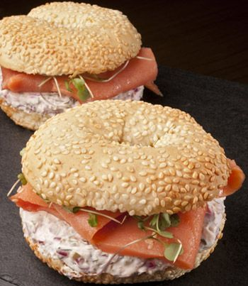 sanduíche de salmão com cream cheese, cebola roxa e no pão bagel