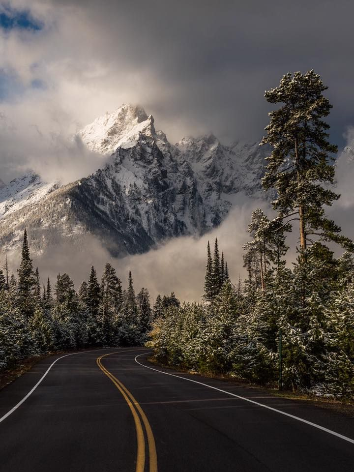 Majestic Places to See in Wyoming Perfect for Every Outdoor Enthusiast Grand Teton National Park in Wyoming with curling clouds and snow-dusted peaks. Photographer Eric Adams