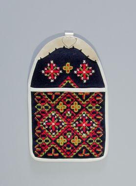 Kjolsäck till dräkt för kvinna från Nås socken, Dalarna. Modell med avskuret framstycke. Tillverkad av mörkblått ylletyg, vadmal, med broderier av ullgarn i rött, grönt och vitt, plattsöm, stjälksöm och sticksöm. Yttäckande motiv byggt på upprepade snedställda fyrkanter med inkomponerade korsornament, samma dekorelement återkommande på överstycket. Kantning av vitt fårskinn. Bygel av vitmetall med fast krok, lätt gultonad, graverad dekor. Foder och bakstycke av svart bomullspoplin.