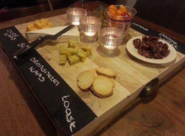 Leuk met een feestje met diverse salades, kazen, noem maar op. Een houten snijplank, schoolbordverf en een krijtje!