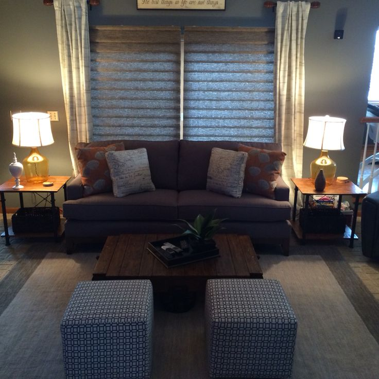 Family room in gray, burnt orange and cream. Sofa, industrial style coffee table, cube ottomans, area rug