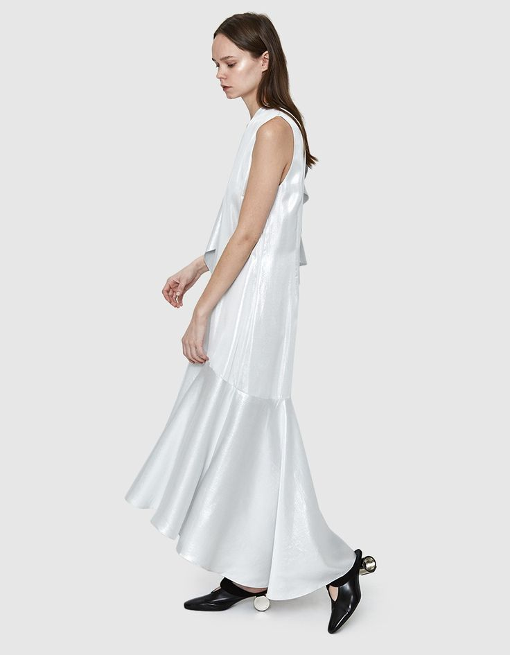 Occasion dress from Rodebjer in Silver. High neckline. Sleeveless. Double-button closure at chest. Adjustable overlay can be worn multiple ways. Cascading ruffles at skirt sewn on a bias. Asymmetrical hem. Unlined. Ankle length. • Metallic Silk Blend