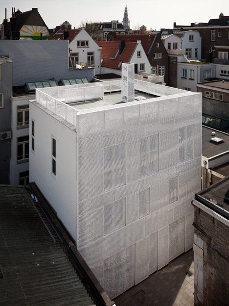 Dutch designer Chris Kabel has wrapped this house and studio in Amsterdam with a facade of perforated hexagons that catches the light like a hanging sheet of fabric.