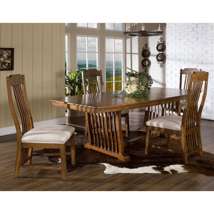 This trestle table is made of hardwood solids and veneers. This furniture piece shines with a medium brown oak finish and features walnut diamond inlay accents.
