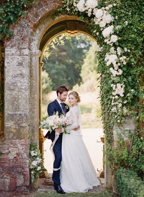 Kent florist Jennifer Pinder for a botanical inspired wedding at Falconhurst wedding venue in Kent with pale pink and white tones photos by Julie Michaelson. A floral arch created by Jennifer Pinder using soft pink roses that are tucked into the naturally growing ivy on this beautiful stone arch. A classic English garden wedding.