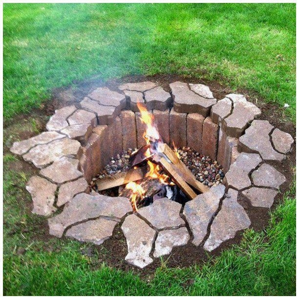 backyard fire pit, lined with firebricks and gravel surrounded by paving stones.