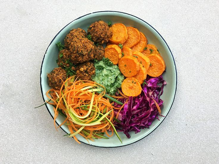 These Buddha bowls are filled vegan & gluten free lentil meatballs, roasted and raw vegetables all topped with a creamy Avocado herb sauce. #healthyRecipe