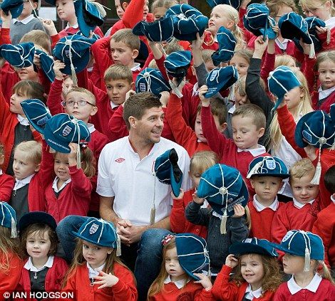 All smiles: Gerrard poses with the kids in celebration of his 100th cap with England. Lad.