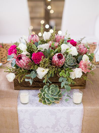 """This dark wood makes the floral arrangements in lighter wood look a little more upscale """"country."""""""