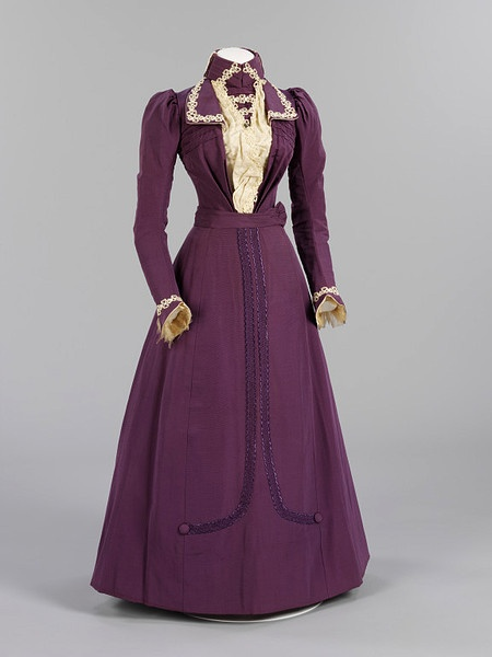Wedding dress. 1899. London. Purple ribbed silk jacket bodice and skirt. The jacket has cream satin drapery down the front, overlaid with white machine lace and braid trimming. The flared cuffs of the sleeves are faced with cream satin and chiffon wrist ruffles. The front of the skirt is trimmed with applied braid and covered buttons. The ensemble is accompanied by wax orange blossom hat trimming.
