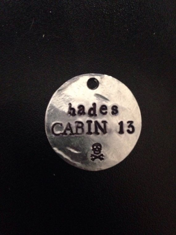 PRODUCT INFORMATION: - Made on a 1 inch aluminum blank (wearer friendly) - Hangs on a black adjustable cord, about 26 inches at the largest setting - The words HADES CABIN 13 and a skull and crossbones are stamped on the pendant - These are HANDMADE so they will not be 100% exact copies of what you see in the picture.  SHIPPING INFORMATION: - These are not pre-made meaning that I make them as they are ordered - I make my pendants in the order that they are received - The making and packaging…