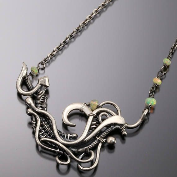 A beautiful swirling of fine silver wire that has been hand-shaped and woven together. Nestled into the woven form are tiny Ethiopian Opals. Pendant length: 1 inch Pendant width: 1-3/4 inches Necklace length: 18 inhces All the jewelry in my shop are my own design and crafted by me. I take great joy in making each piece and love the the challenge of taking a thought, idea, or the random imaginings of my wandering mind and translating it into the wire.