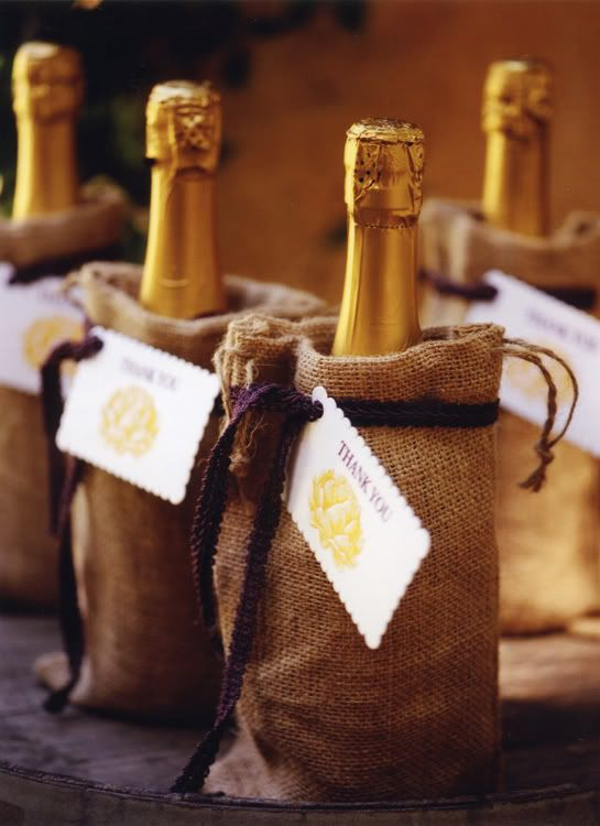 Splits of champagne are wrapped in little burlap sacks from Shibata, and finished with eggplant purple ribbon and a scallop-edged tag. The bubbly favors are displayed on a wine barrel.
