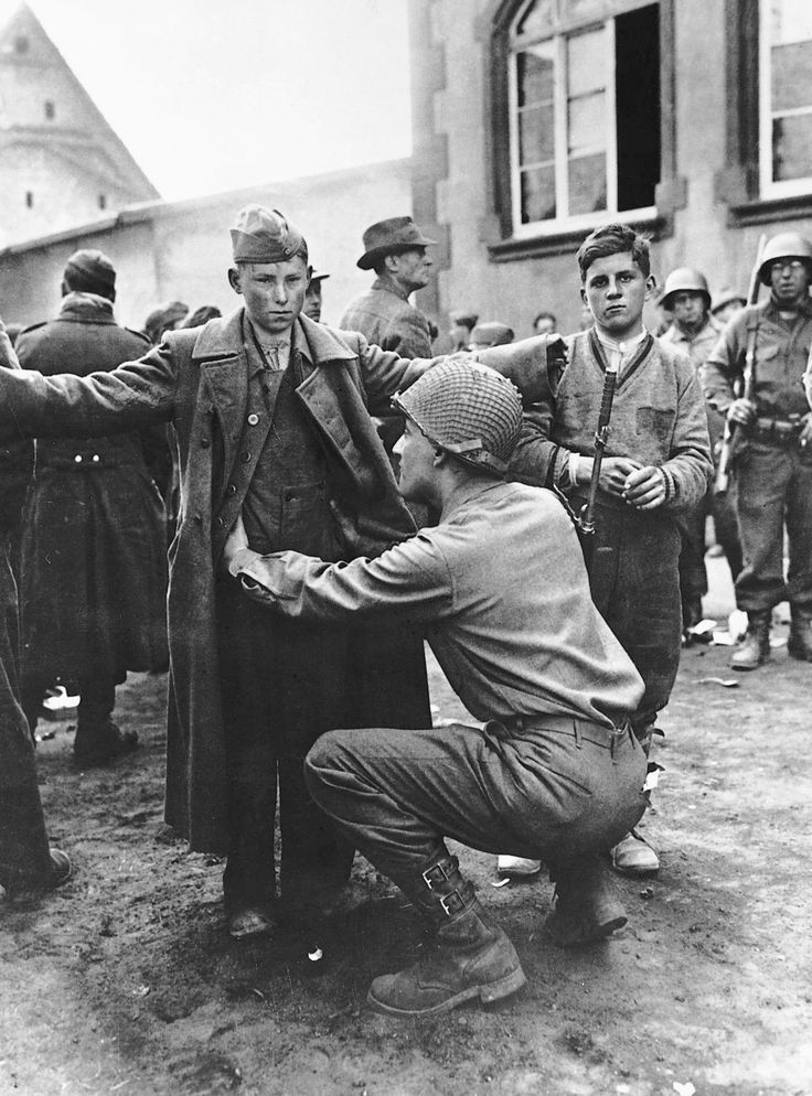 A teenager German gunner receives a pat down after surrendering to the US Army near Berlin, April 1945. Note the boy standing on the right who is wearing army boots but civilian clothing waiting his turn.