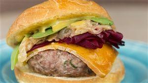 Gros plan sur un hamburger avec une boulette de porc, une tranche de fromage épais et une chiffonnade de betteraves.