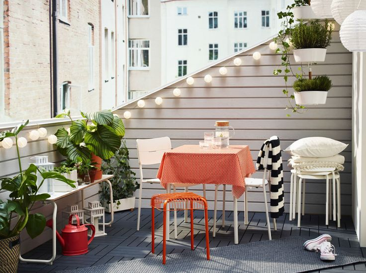 A balcony furnished with a small foldable table, a bench and two chairs, all in white. Completed with extra stools, lanterns, cushions and blankets.