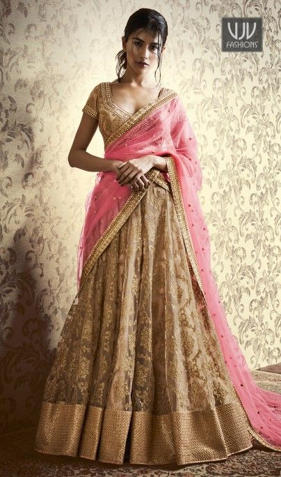 Phenomenal Beige And Pink Color Lehenga Choli This pretty piece is a fairy tale that begins to unfold as you reveal your beauty in it. Look ethnic in this affluent beige and pink art silk and net a line lehenga choli. Beautified and stylized with patch border, stone and zari work to give you an attractive look. Comes with matching choli and dupatta.