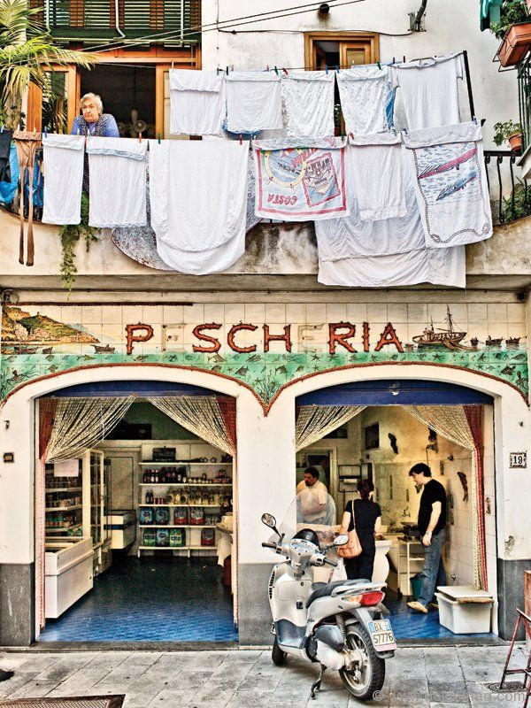 Pescheria (fish shop) and Italian woman in window, Amalfi Village. Photo by Robert Leon