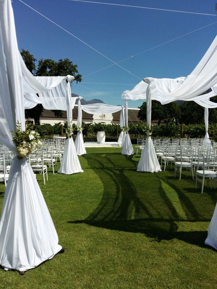 OKASIE | Draped ceremony seating decorated with floral posies.