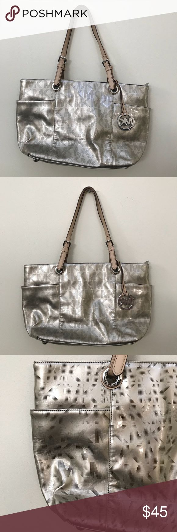 Michael Kors MK signature metallic silver tote bag Michael Kors MK signature metallic silver tote bag  Preowned condition with where to bottom, corners and strap. This was used for two seasons then stored in a tote, with minor wear from storage. Some markings on internal area inside. Perfect for school, career, work or weekend bag. Great size to bring on airplane for travel as personal item.   Bundle and save with other items in my closet,   I ship same or next day from Ohio! MICHAEL Michael…