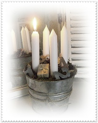Tall, thick candles in a pail, backed by mirror to reflect the light - Advent