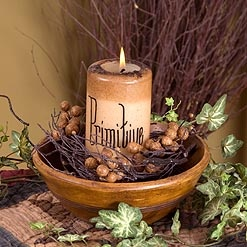 A locally handpainted primitive candle settled inside a reproduction treen yellow ware bowl accented with a mustard cluster berry ring. An adorable midsize centerpiece.