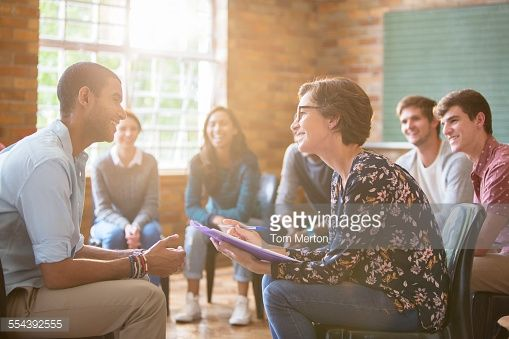 Stock Photo : Group watching man and woman talking in group therapy session