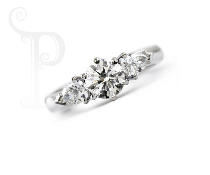 Handmade Platinum Trilogy Ring, With a Round Brilliant Diamond Centre with two Pear cut Diamonds either side.
