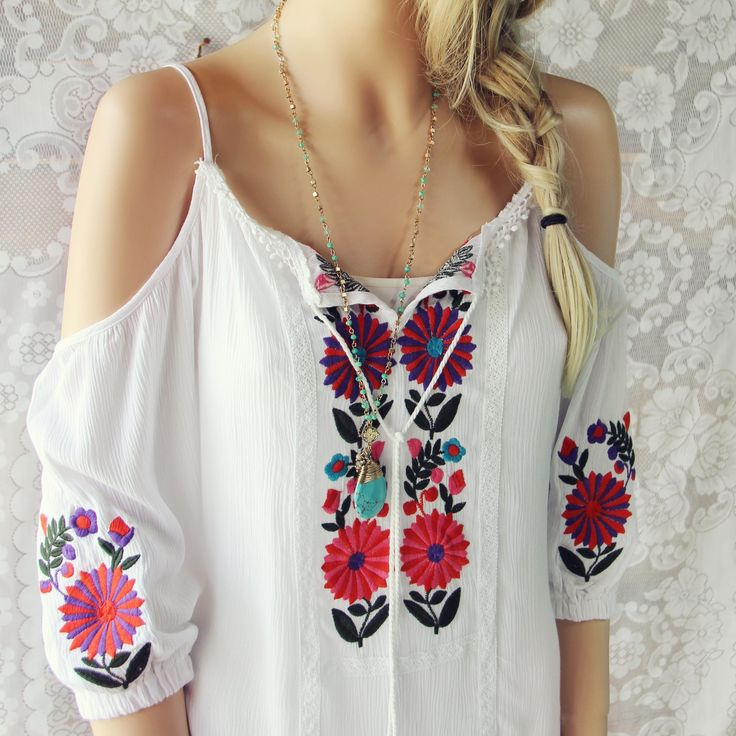 Gorgeous Mexican embroidered details adorn this bohemian tunic dress. Designed with a white base, off-the-shoulder sleeves, front tassel tie, and embroidered details throughout. Perfect paired with sandals for a breezy summer outfit. One size for small, medium,