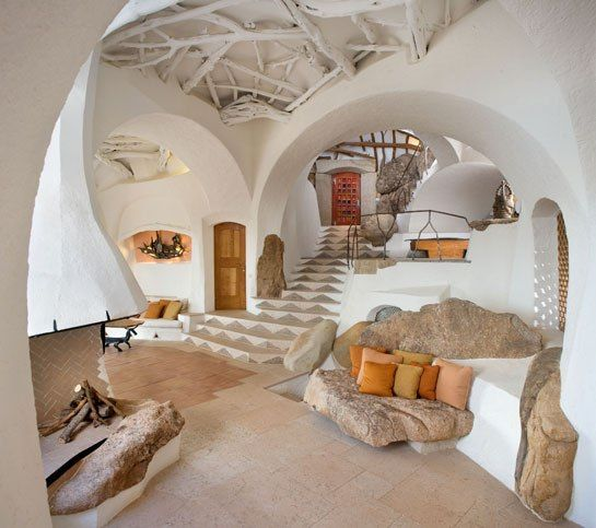 sculptural home on Sardinia's northwest coast utilized on-site boulders for sofas, room dividers, and a hearth.